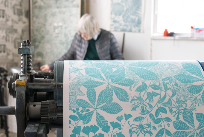 Marthe's studio with her in the background, some fabric designs on the wall and a hand printed design in the front