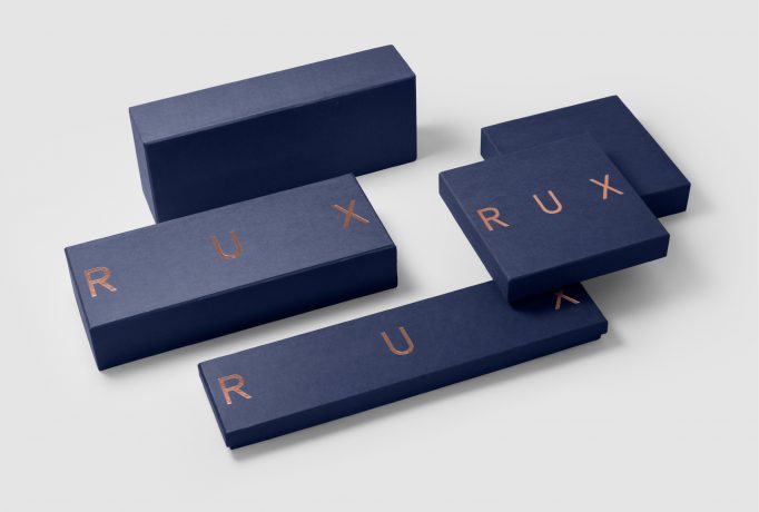 different sizes of dark blue boxes with 'RUX' written in copper