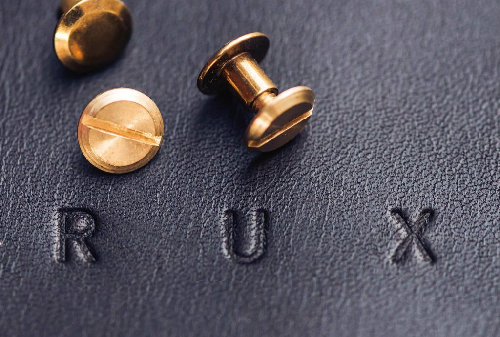 'RUX' blind embossed into black leather and three golden screw nearby
