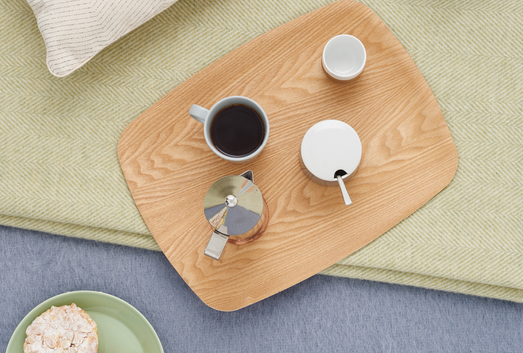 wooden plate with a cup of coffee, sugar and a metal can, on a green blanked