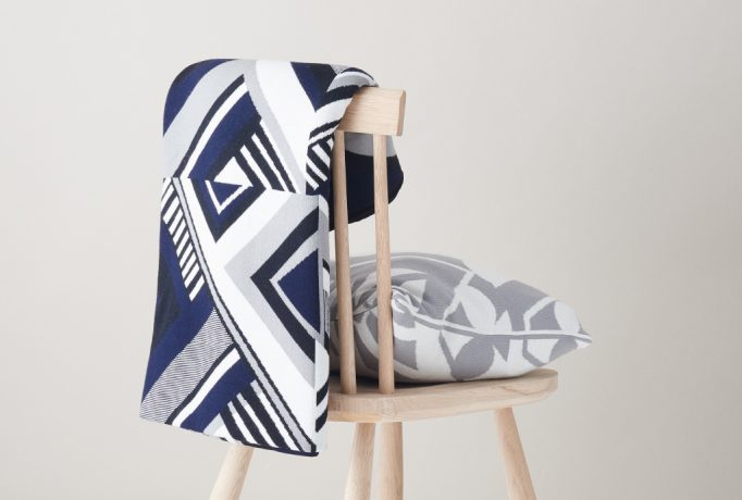 a wooden chair with a white, grey and blue pattern blanked over the backrest and a grey and white pillow on the seat