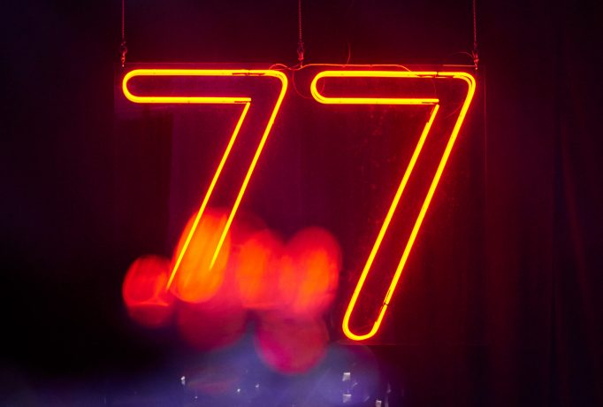 orange neon lights forming the number 77 on a dark blue background with some red light spots