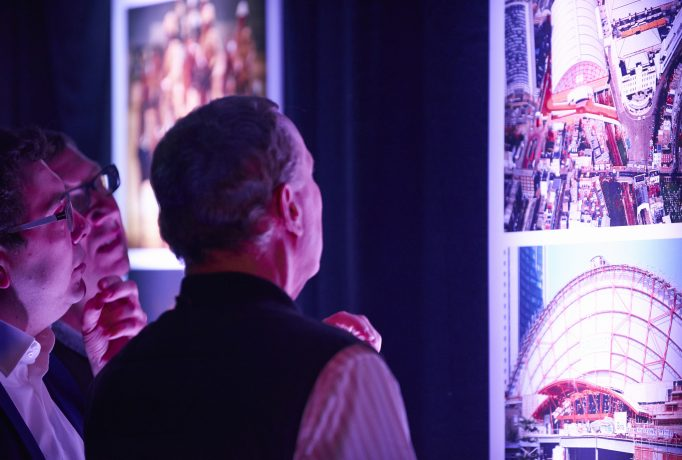 people looking at shining photographs in a dark room
