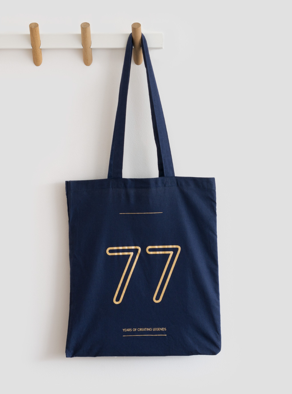 dark blue bag, with the number 77 written in orange, on a hook