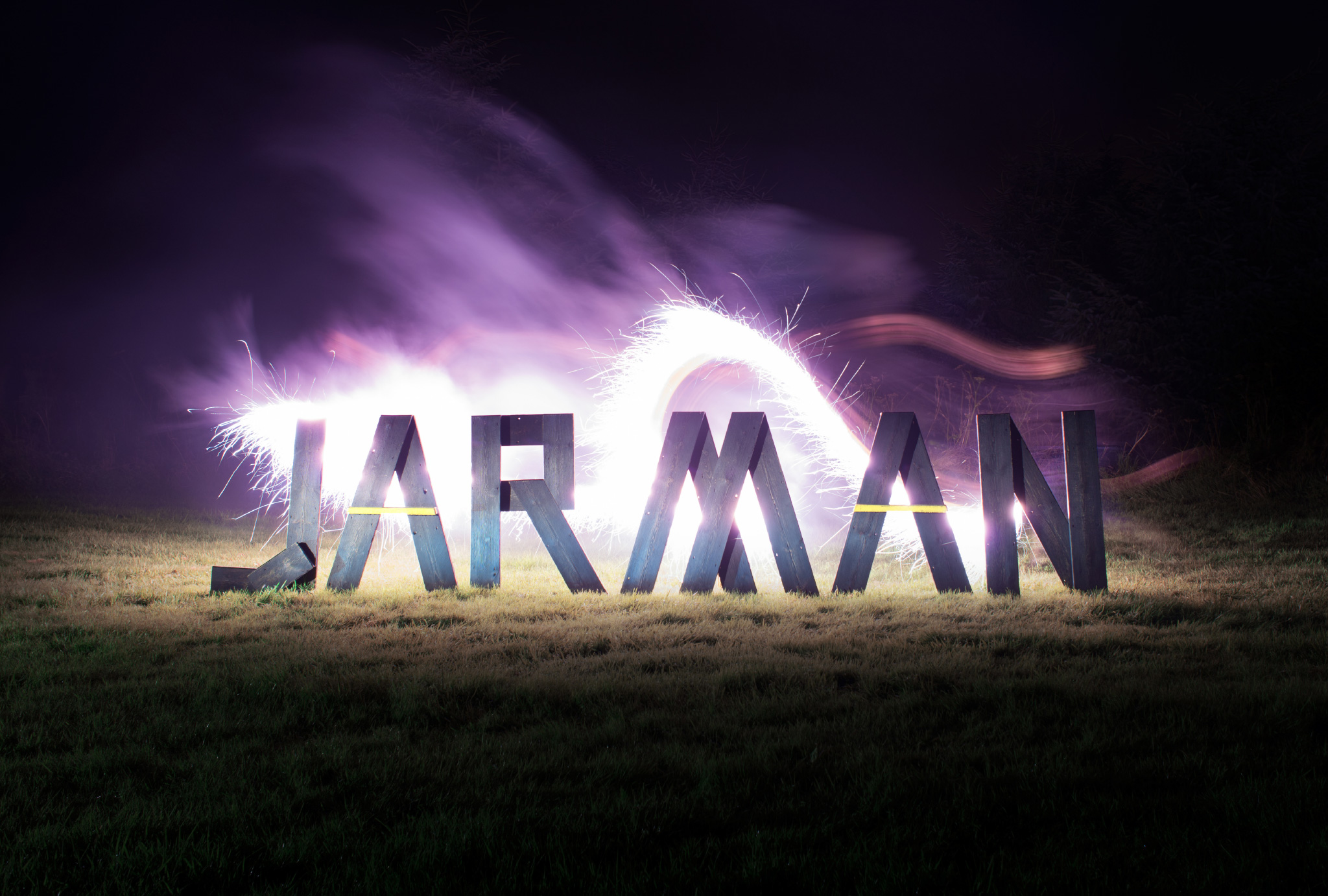 word 'JARMAN' made out of wooden letters standing on grass, in front of bright flair
