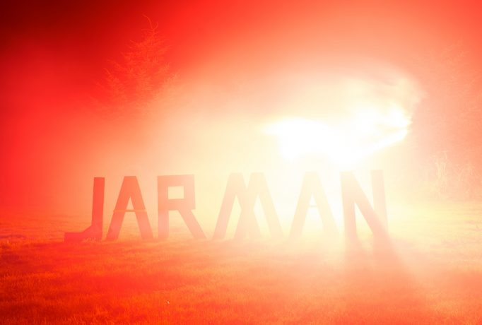 word 'JARMAN' made out of wooden letters standing on grass, illuminated by a red smoke flair