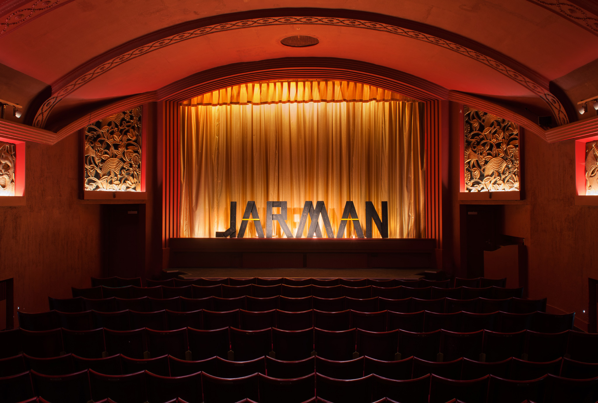 old cinema with red walls, word 'JARMAN' made out of wooden letters standing on the stage