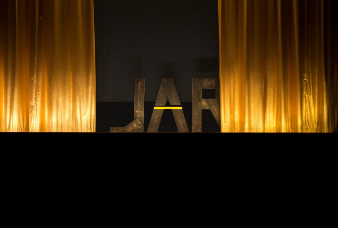 letters 'JAR' made out of wood standing in the back between two golden curtain