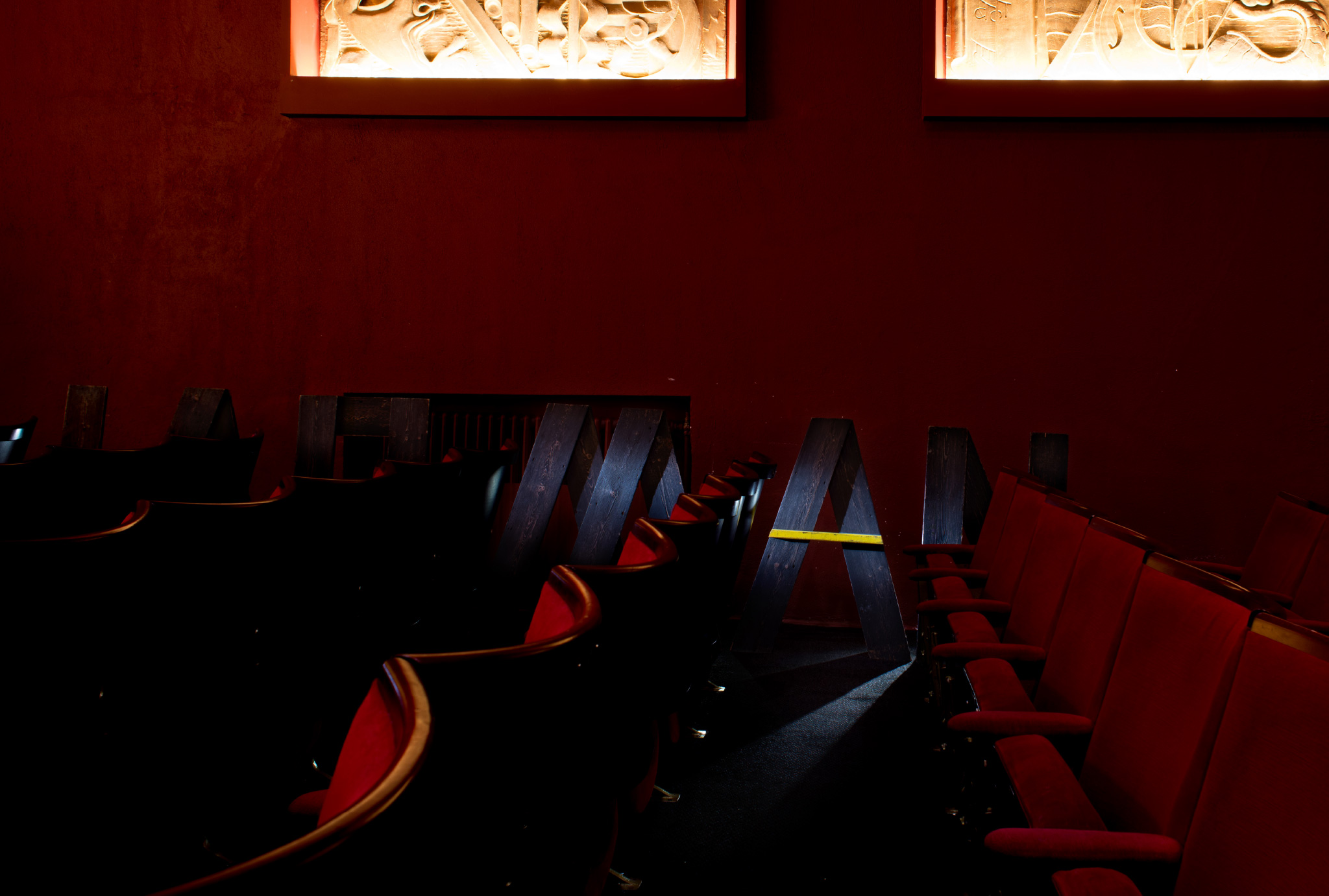 red cinema seats in front of wooden letters