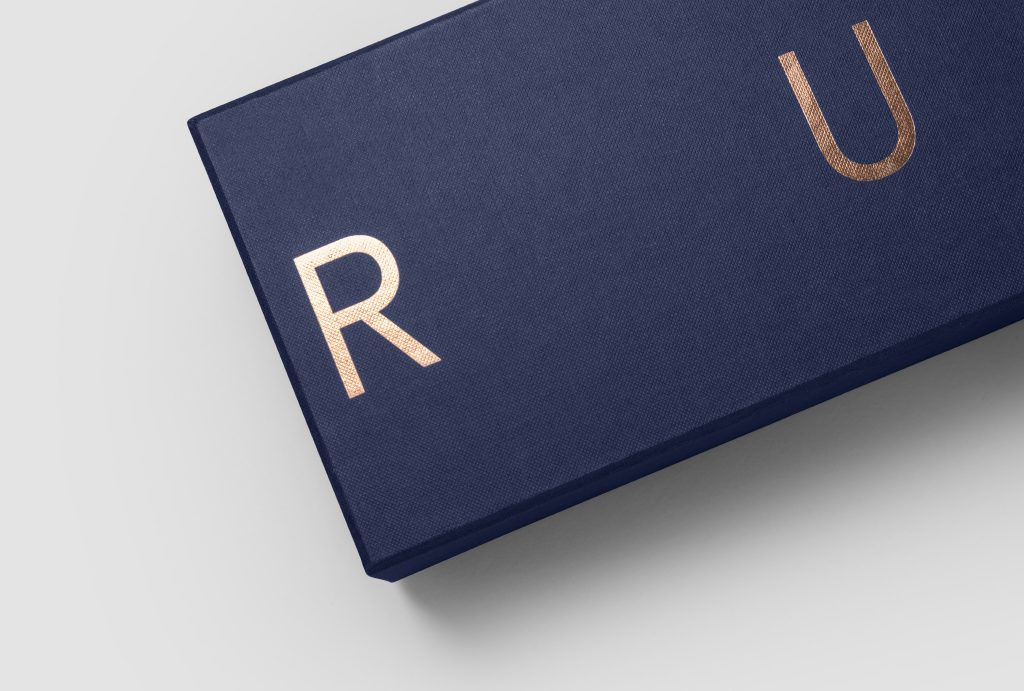 close up on a dark blue box with copper 'RUX' logo