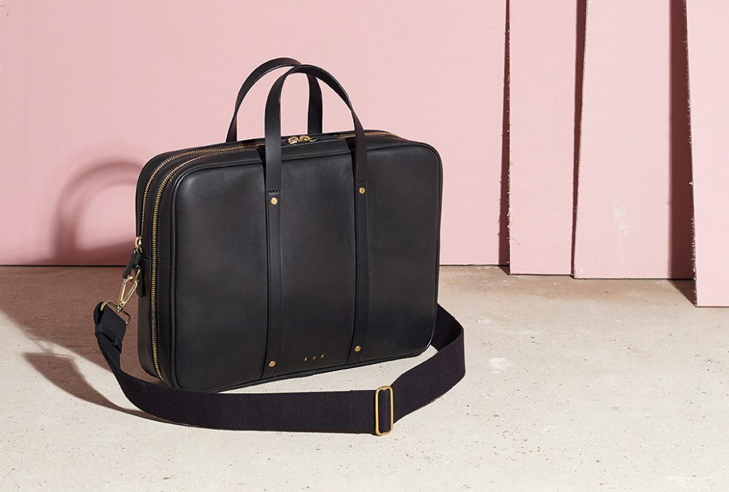 black men's leather bag standing on a grey floor with pink walls