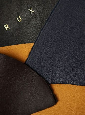 close up on leather in yellow, dark blue and black with 'RUX' logo foiled in gold