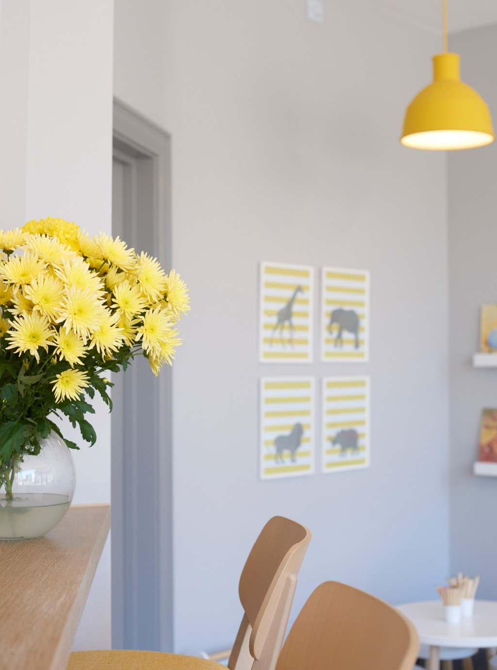 grey wall with four yellow pictures on it, yellow flowers and wooden chairs in the front and a yellow drop light