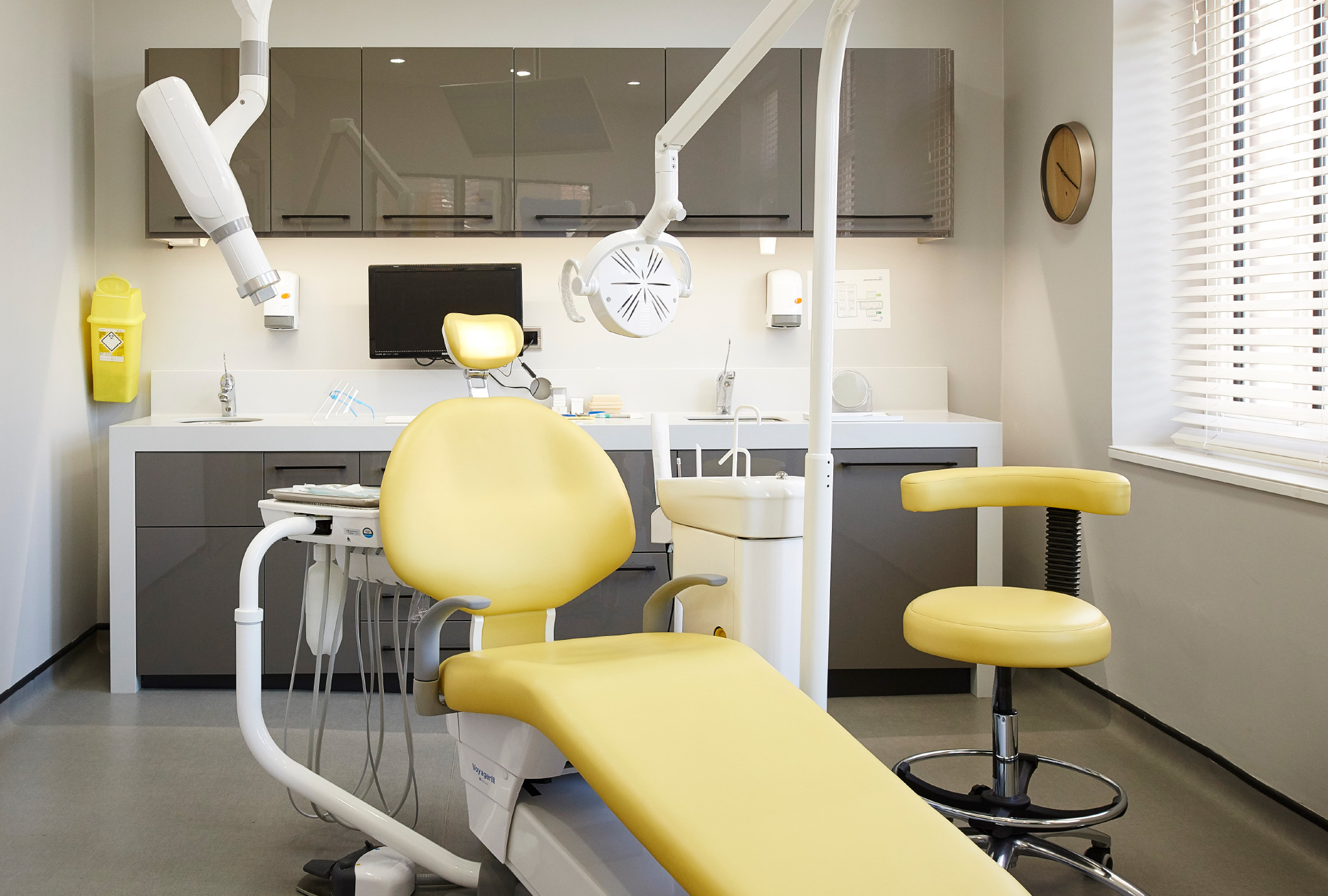 yellow dentist chair in front of a dark grey counter