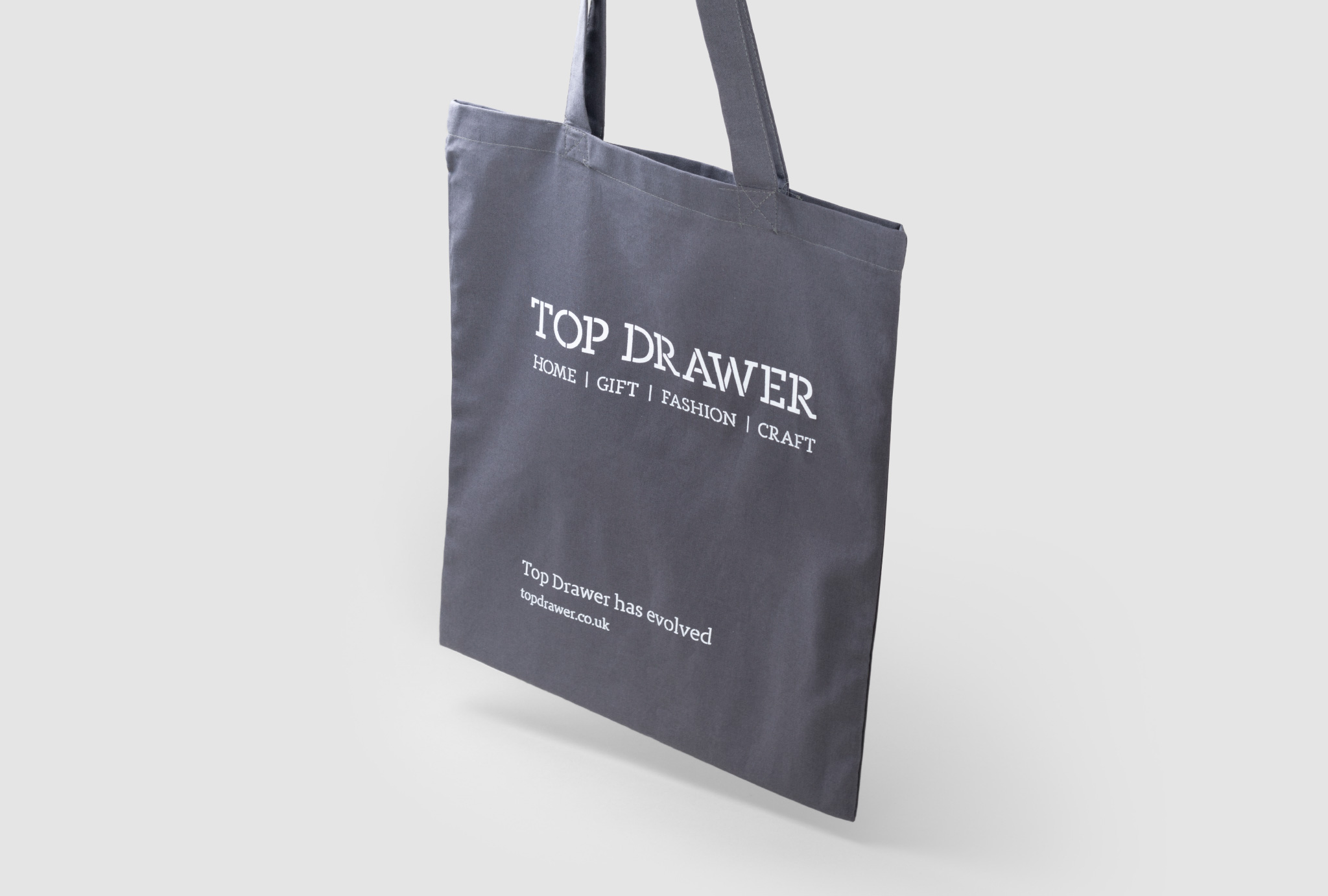 dark grey bag that says 'TOP DRAWER' 'HOME / GIFT / FASHION / CRAFT' in white