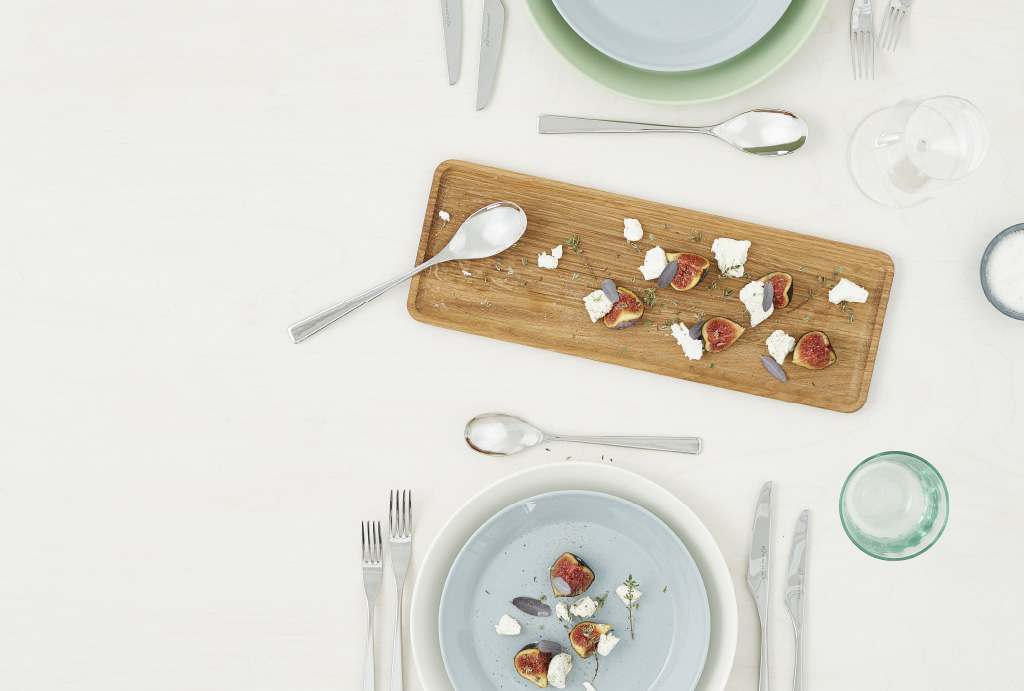 view from above on two plates with cutlery glasses and figs with goat cheese on a wooden plate