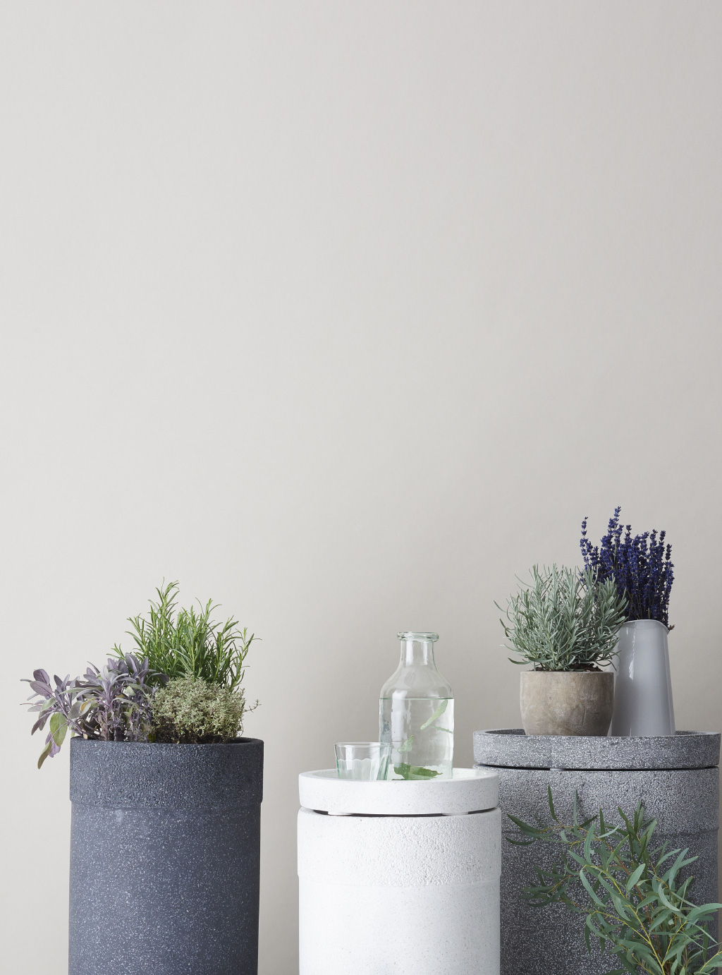 three concrete plinths, two grey with plants on top and one white with a glass and a bottle with water