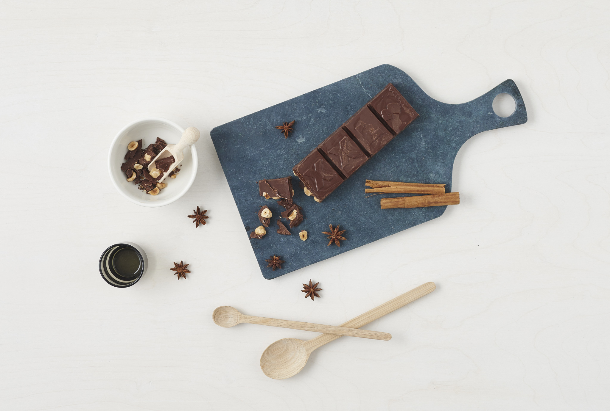 grey cutting board with chocolate and cinnamon on it, two spoons and a cup on a table