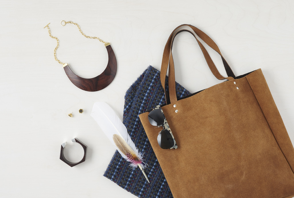 a brown wild leather bag with sunglasses on it, feathers, jewellery and a blanked photographed from above