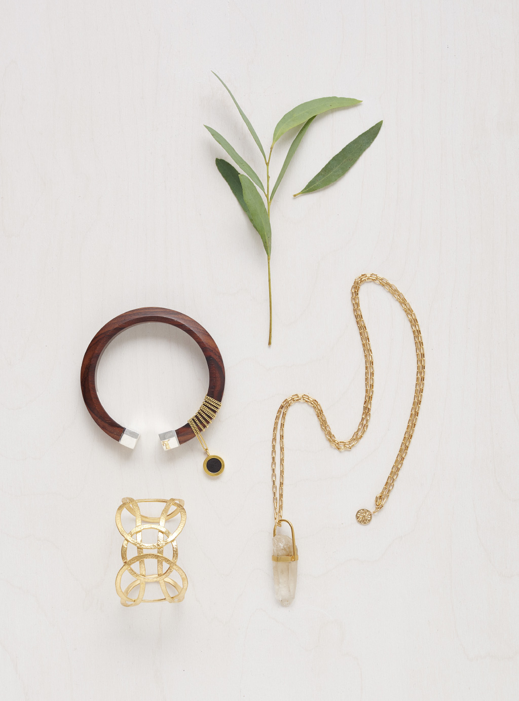 a golden necklace, a golden and a wooden bracelet and a branch
