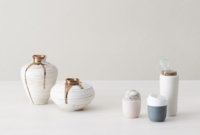 two white vases with gold drips and three different shaped cups