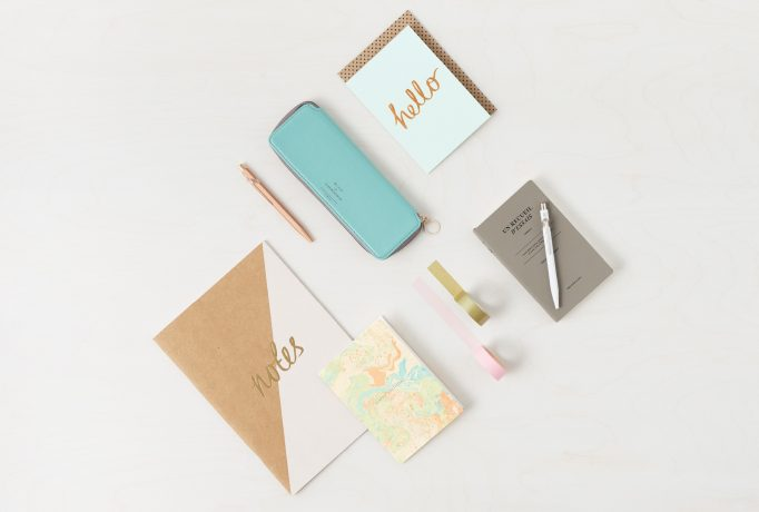 a brown and a white pen, a blue case, a notebook and tapes photographed on a table