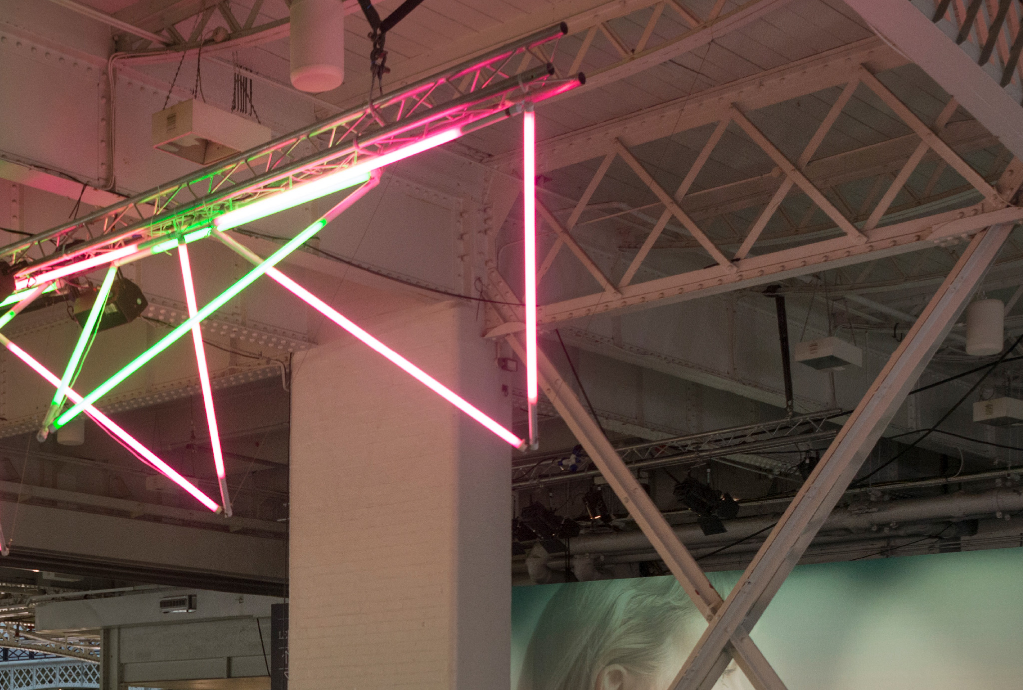 green and pink neon tube hanging from the ceiling