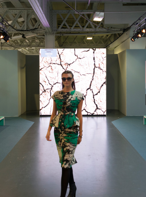 front view at the catwalk, one woman with a green, black and white dress
