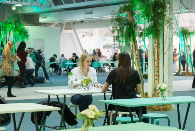 exhibition design with tables and chairs, some plants around with green lights