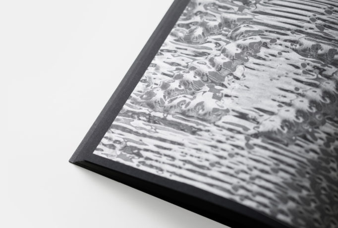 close up of an image of magnetically manipulated ferrofluid in a black book