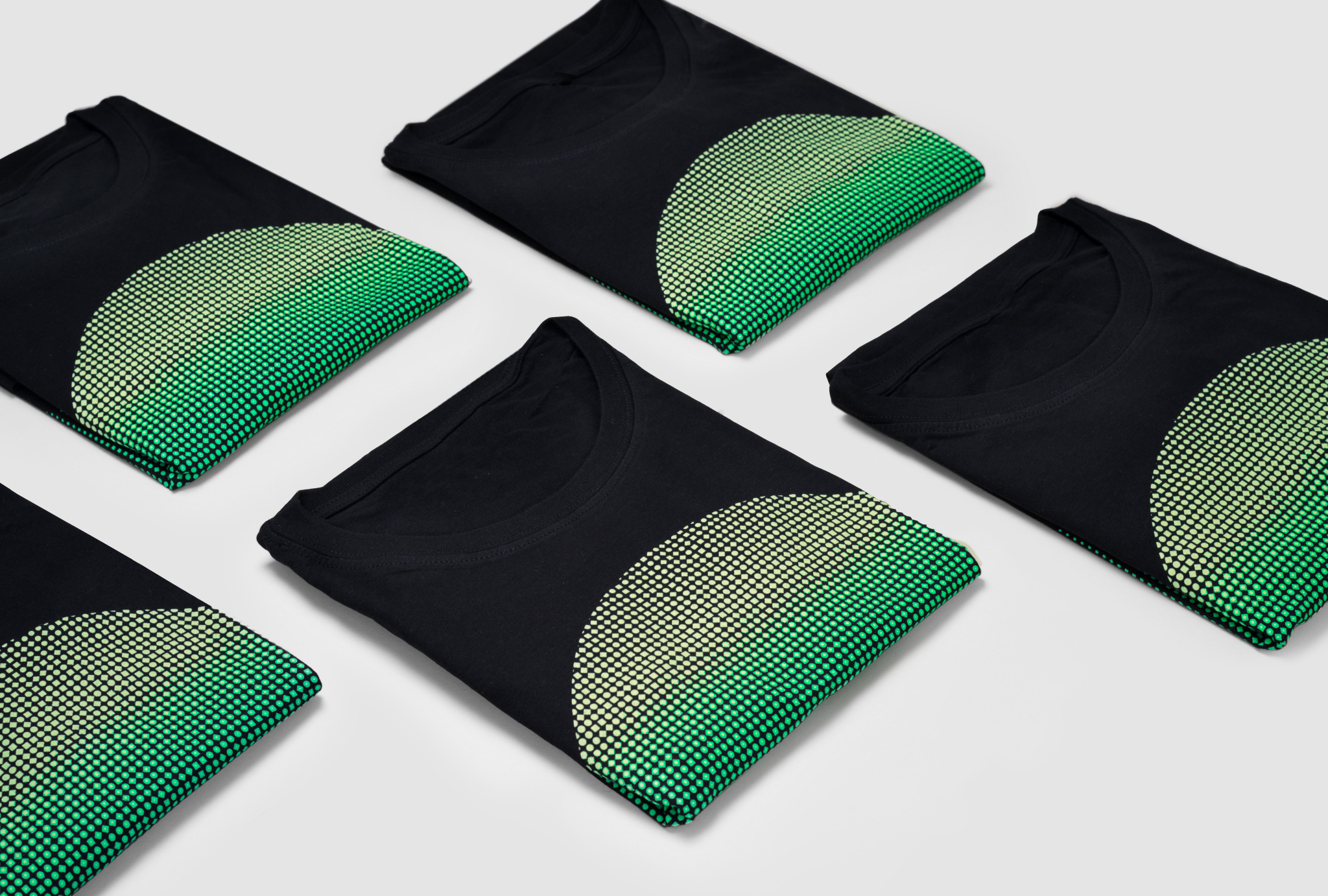 folden black t-shirts with printed green circle next to each other