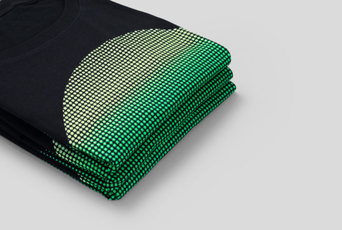 pile of folded black t-shirts with printed green circle