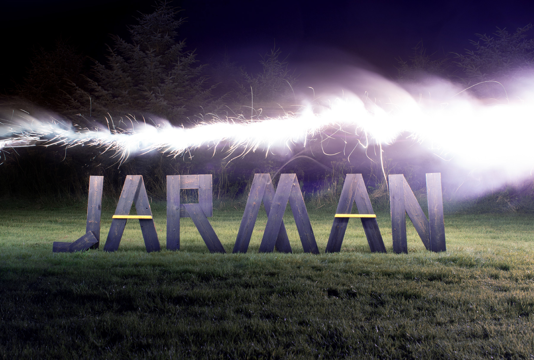 art-direction for JARMAN awards consisting of wooden letters in a dark field, illuminated by a flair