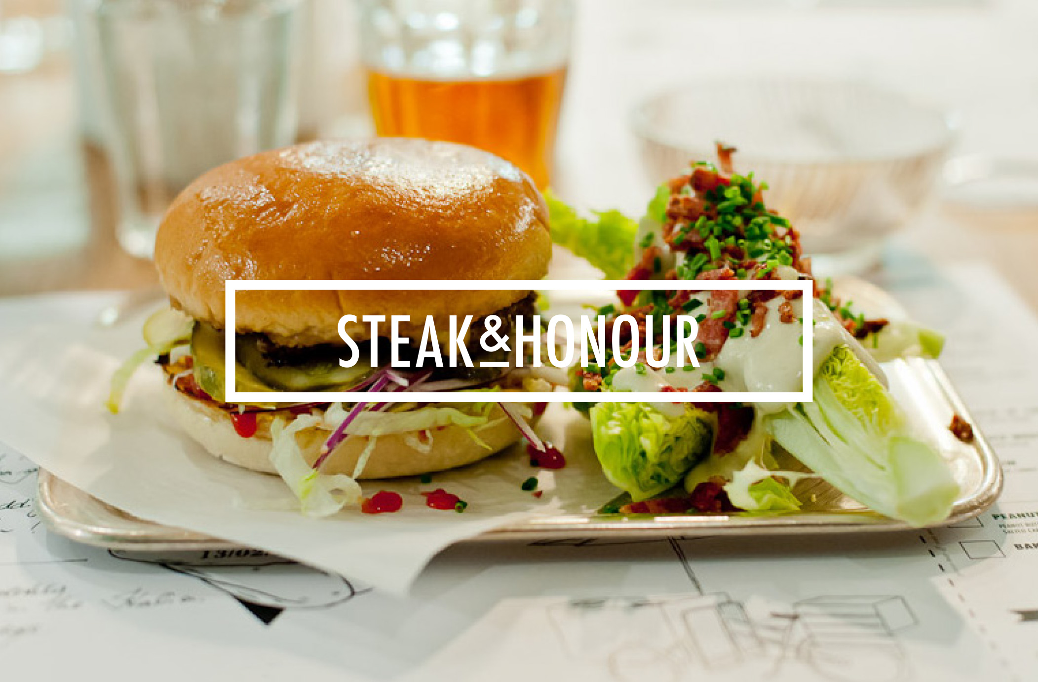 burger and salad on a plate with white 'STEAK & HONOUR' written block in front