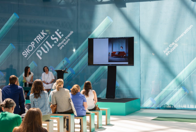 design of ShopTalk seminar area showing large printed drape and TV screen. Audience sit on benches in front of stage